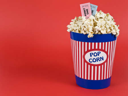 bowls of popcorn: A popcorn bucket over a red background. Movie stubs sitting over the popcorn.