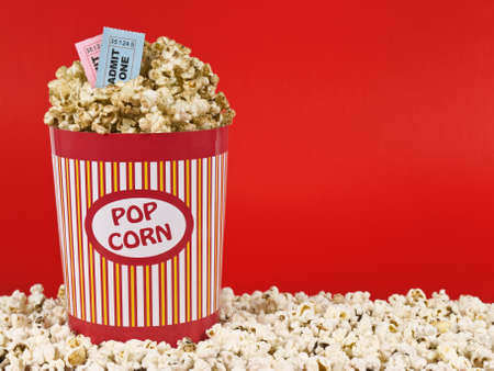 admit one: A popcorn bucket over a red background. Movie stubs sitting over the popcorn.