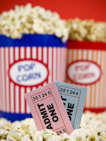 Two popcorn buckets over a red background. Movie stubs sitting over the popcorn. Stock Photo - 4541293