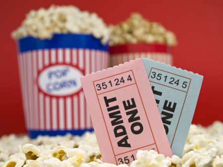 Two popcorn buckets over a red background. Movie stubs sitting over the popcorn. Stock Photo