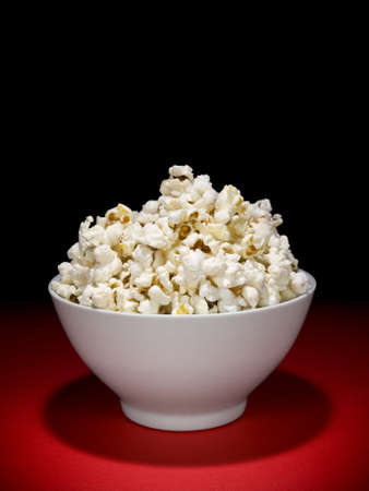 popcorn bowls: A bow full of popcorn under the spotligh. Stock Photo