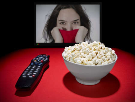 A popcorn bowl and a remote control. A wide TV screen as a background.