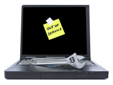Laptop with an Out of Service sticky note and a spanner over the keyboard. Isolated on white.