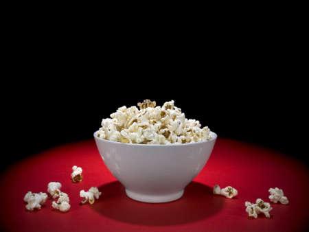 A bowl full of popcorn under the spotlight. Stock Photo
