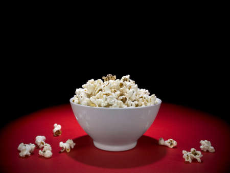 A bowl full of popcorn under the spotlight. Stock Photo