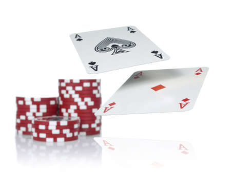 Two aces flying over a game table beside three piles of red chips. Isolated on white. Stock Photo - 4650547