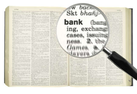A magnifying glass on the word BANK on a dictionary. photo