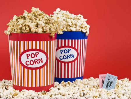 Two popcorn buckets over a red background. Stock Photo