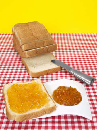 A slice of bread spread with jam beside a loaf of sliced bread. photo