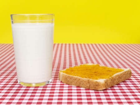 A glass of milk and a toast spread with jam over the table. photo