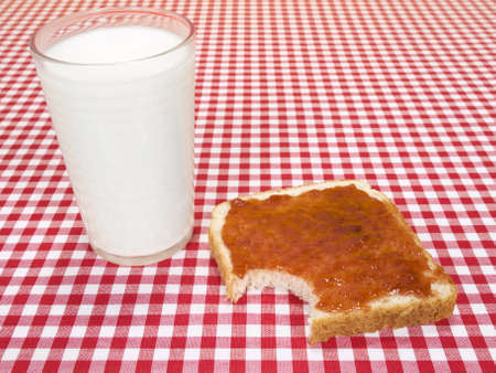 A glass of milk and a toast spread with jam, with a bite missing. photo