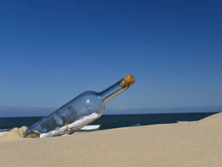 writing on glass: A bottle with a message inside is buried on the beach. Stock Photo