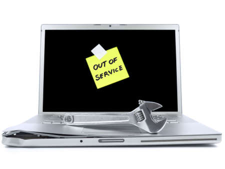 Damaged laptop with a post-it saying Out of Service and a spanner over it. Isolated on white.