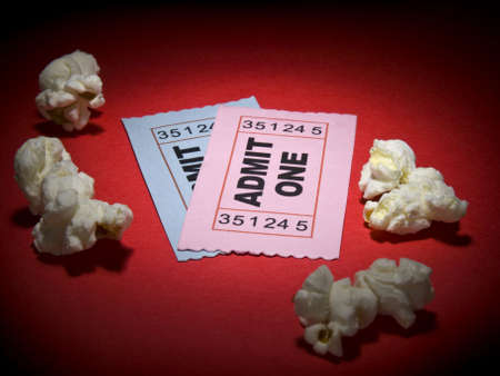 Close up shot of two generic admission tickets and some popcorns arround. photo