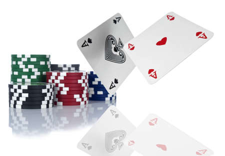 Two aces are about to land beside a stack of gambling chips. Isolated on white.