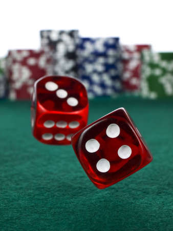 3 4 length: Two red dices rolling over a green felt. Out of focus stack of colorful chips on the background. Stock Photo