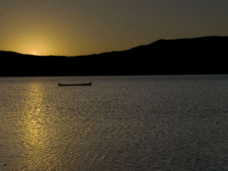 The sun behind the mountains is reflected over the lake surface, beside an abandoned boat. photo