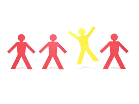 A yellow paper figure is celebrating between other red paper figures. photo