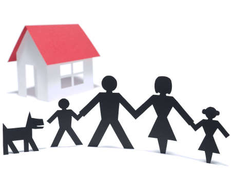 A paper family is holding hands beside their new paper house. Even the paper dog is there.