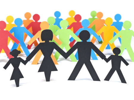 A paper family holding hands in front of a group of multicolor paper men.