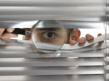peep: A man is peeping through the blinds with a magnifying glass.