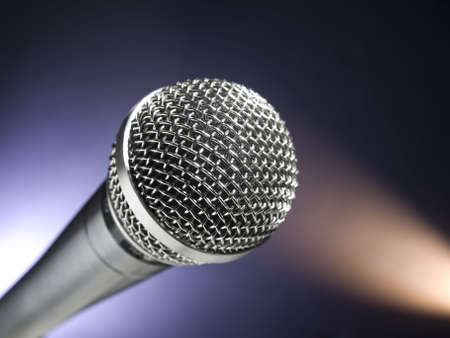 A dynamic microphone on stage. Color spot lights as background. photo