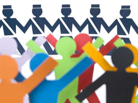 Several color paper figures standing before the paper police. Stock Photo - 5040273