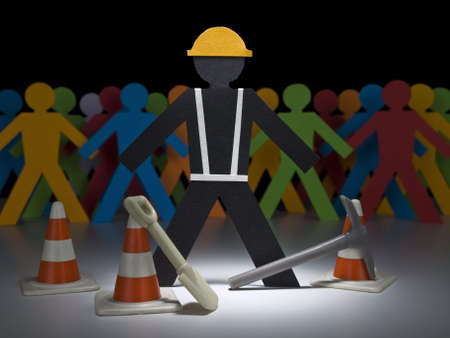 A paper construction worker stands on the spotlight with his tools and cones. photo