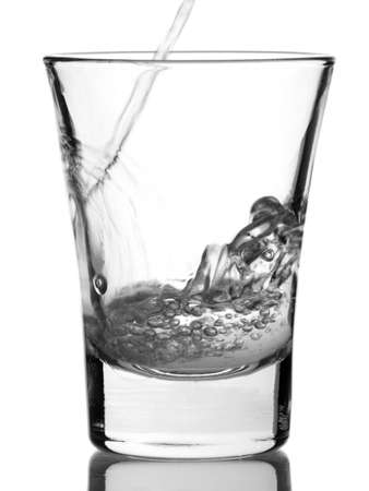 Pouring a shot of vodka with reflex on white background. Stock Photo - 5254251