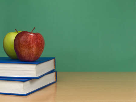 A blank chalkboard with two apples over books. photo