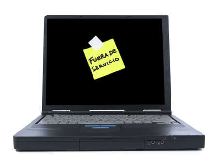 todo: Black laptop with a sticky note in spanish meaning Out of Service. Isolated on white.