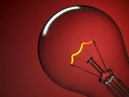 Close up on a transparent light bulb over a red background. photo