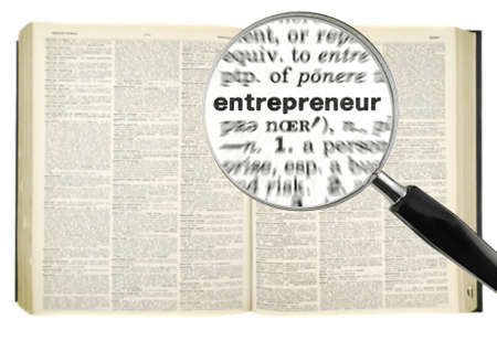 A magnifying glass on the word ENTREPRENEUR on a dictionary. Isolated on white. photo