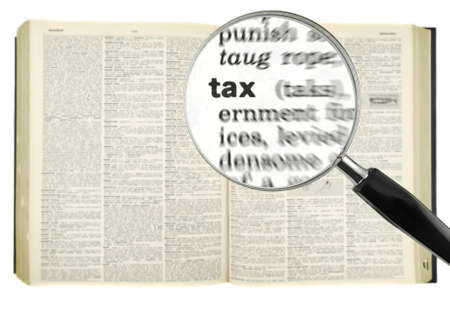 A magnifying glass on the word TAX on a dictionary. Isolated on white. photo
