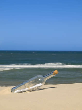 A bottle with a message inside is buried on the beach. Stock Photo