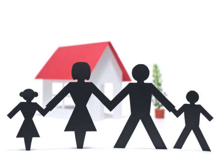 A paper family is holding hands beside their new paper house. photo