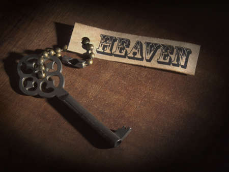 tarnish: An old key attached to a label saying HEAVEN over a wooden table. Stock Photo