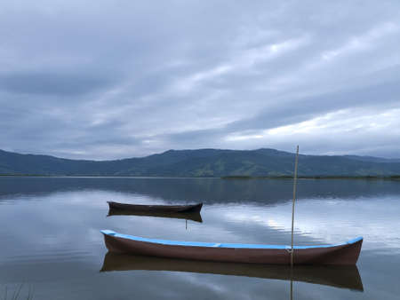 Two canoes tied on a quiet lake under a cloudy sky.