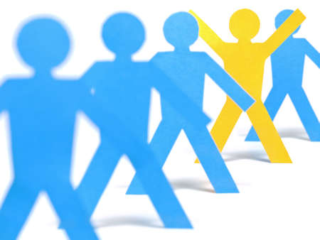 A yellow paper figure is celebrating between other blue paper figures. photo