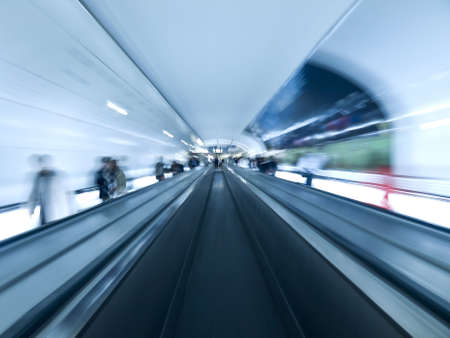 Futuristic image. Blurred people on the walkway tunnel. Empty center lane. Stock Photo