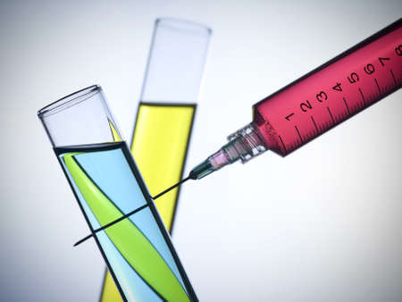 A syringe and two test tubes filled with color liquids. photo