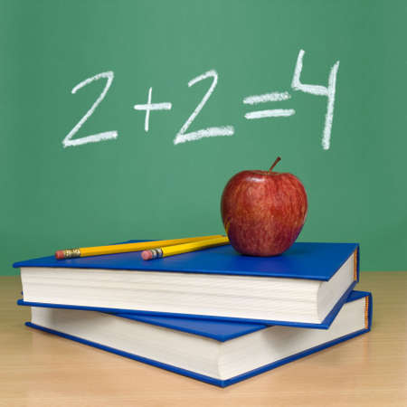 2 + 2 = 4 written on a chalkboard. Books, pencils and an apple on the foreground. photo