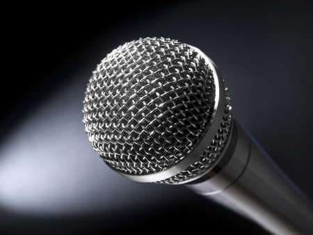 A dynamic microphone on stage. Bright spot light on the background. photo