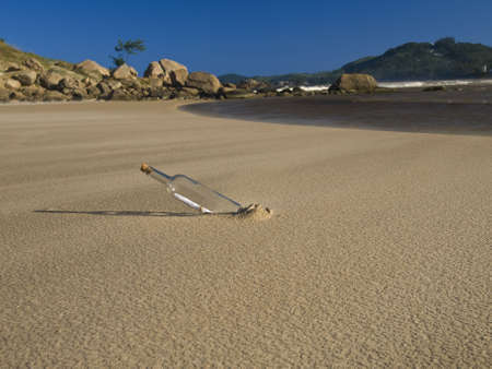 A bottle with a message inside is buried on the beach. Stock Photo - 6398321