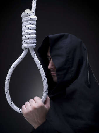 A headsman is looking askance to the camera while holding a noose. photo