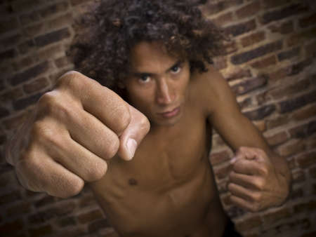 A young man throwing his fist to the camera. Focus on the hand. photo
