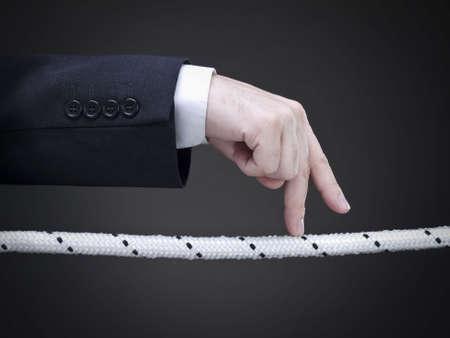 Close up de dedos de un empresario caminar en la cuerda floja. Imagen conceptual.  Foto de archivo