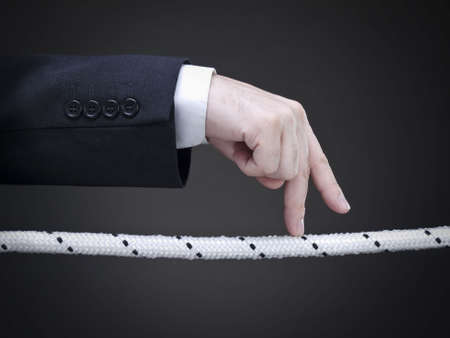 risky: Close up of a businessmans fingers walking on the tightrope. Conceptual image.