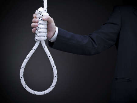 A man on a suit holds a hangman's noose over a gray background.