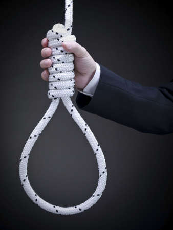 A man on a suit holds a hangmans noose over a gray background.